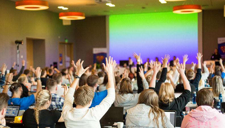Bilde: Fra landsmøte i Pedagogstudentene. Tillitsvalgte viser støtte til taler med døveklapping.