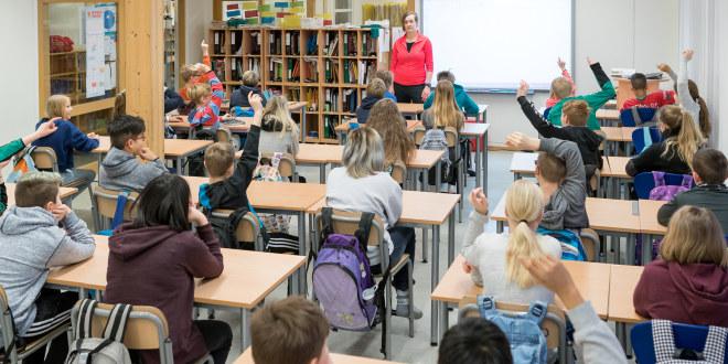 Læreren står foran elevene i klassen, som vi ser bakfra. Det er elever i barneskolen, og det er mange av dem!