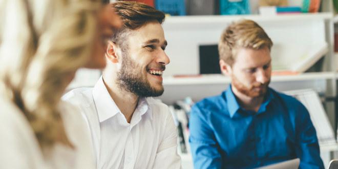 Mannlig lærer smilende sammen med kollegaer.