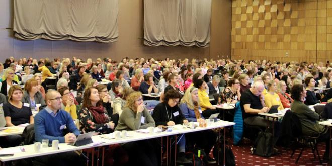 Mange mennesker sitter i en sal.