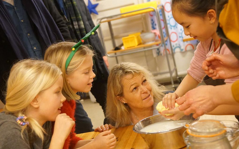 Milla Kalina Harborg Thorn, Olivia Strømmen Nordenström og Jessica Zhou lærer eldre- og folkehelseminister Åse Michaelsen (Frp) å kjerne smør. Statsråden får også smake på linsesuppen som er dagens rett. Foto: Marianne Ruud
