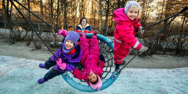Tre barnehagebarn leker på en huske. Det er vinter og de har på seg luer og parkdresser. De smiler og ler. I bakgrunnen står en barnehagelærer og passer på.