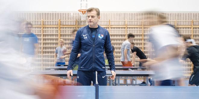 Gymlærer lærer elever å spille bordtennis.