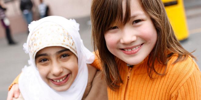 To unge jenter i skolegården smiler til kamera