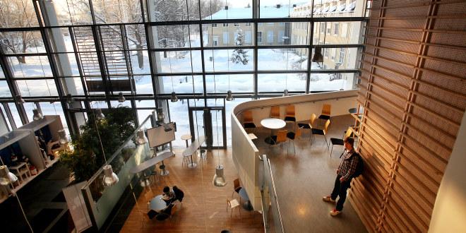 Åpent rom med store vinduer. Små bord med stoler. Noen få studenter sitter og står omkring.