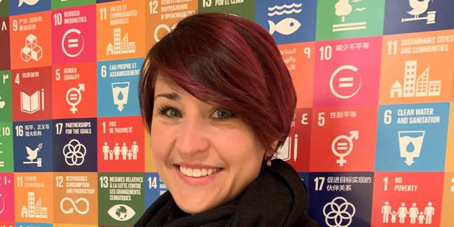 Bilde av Ann Mari Milo Lorentzen foran en plakat av bærekraftsmålene på FNs kvinnekonferanse i New York