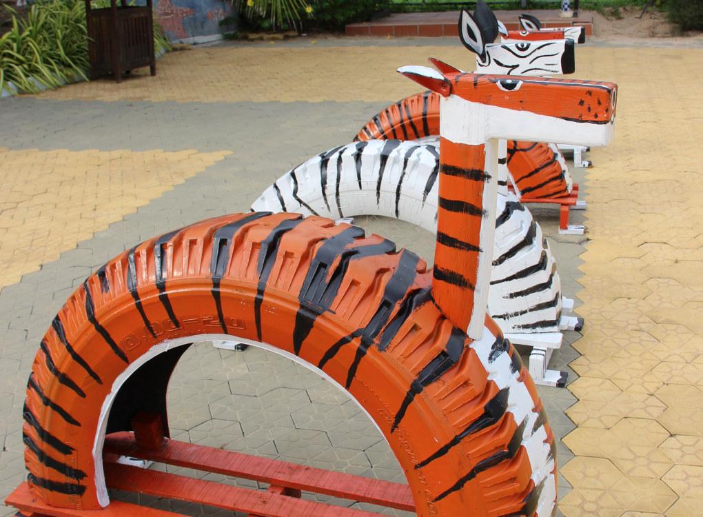 Lekedyrene er laget av gamle bildekk, som er delt i to og malt slik at de ser ut som en tiger eller sebra. Hodet og beina er laget i tre, og barna kan både sitte på dyrene, klatre over og under dem og sitte under dem. De kreative lekedyrene fant Første steg på en lekeplass i Ho Tram i Vietnam. Foto: Line Fredheim Storvik