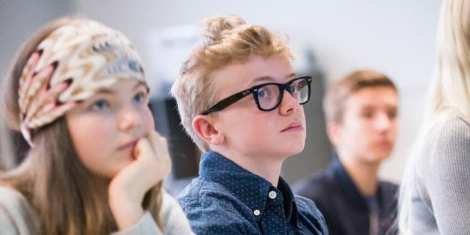 Fotografiet er tatt i et klasserom. Vi ser et nærbilde av tre elever (og ryggen på en). De har blikket vendt antakelig mot en lærer.
