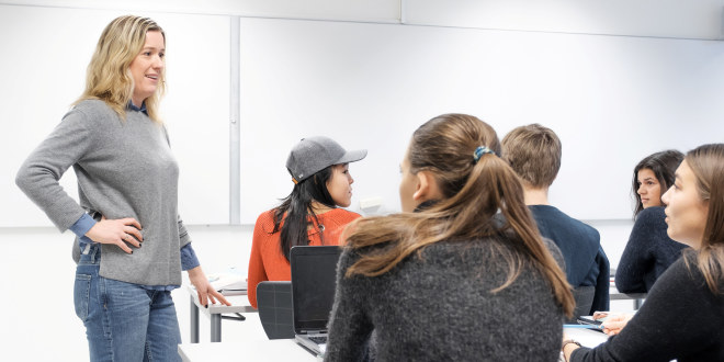 Kvinnelig lærer i dialog med elever i videregående.