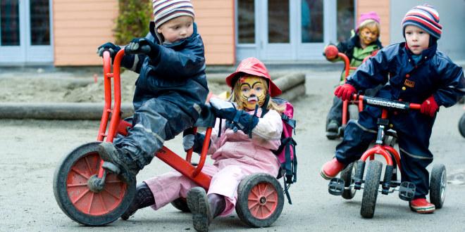 Barn leker på trehjulssykler i barnehagen. En har ansiktsmaling på.