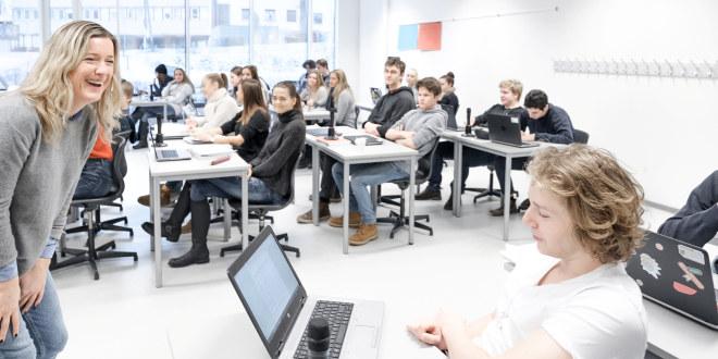 Kvinnelig lærer kommuniserer med elev foran PC i videregående opplæring.