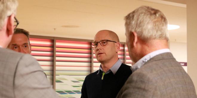 Skallet mann med briller står og snakker med tre andre menn som har delvis ryggen til.