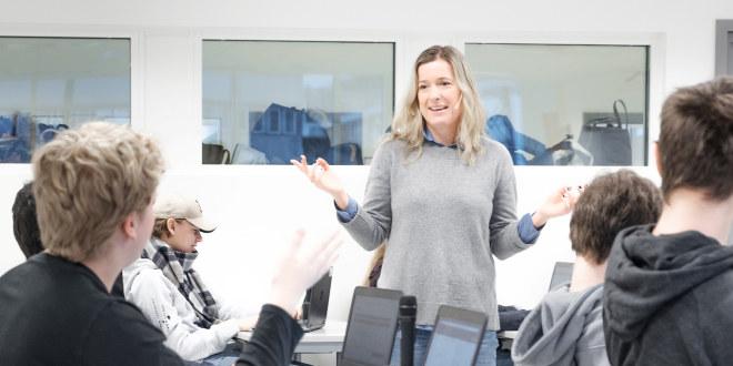 Dame med lyst hår og grå genser slår ut med hendene i et klasserom med elever som sitter ved pultene.