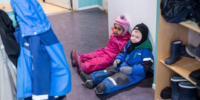 To barnehagebarn sitter påkledd i en gang i barnehagen. De sitter på gulvet. Ved siden av er det en reol med slagstøvler og andre sko.