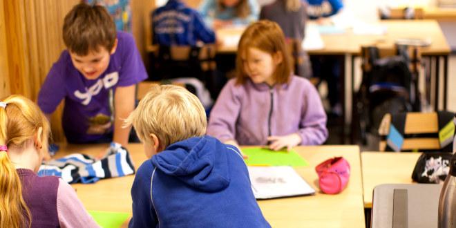 Bildet er tatt i et klasserom. Fire elever er samlet rundt en stor pult. To av elevene har ryggen til fotografen.