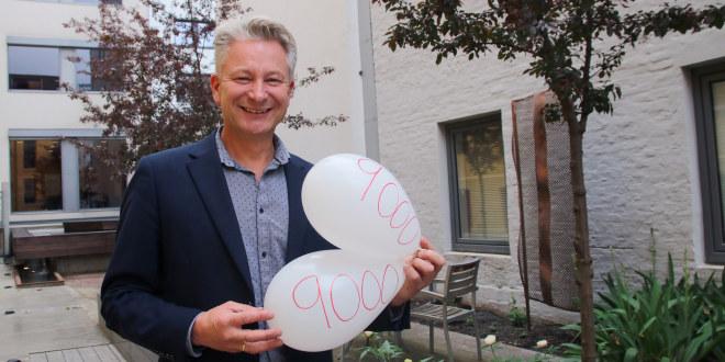 Smilende mann med grått hår holder opp to hvite ballonger hvor det står 9000.