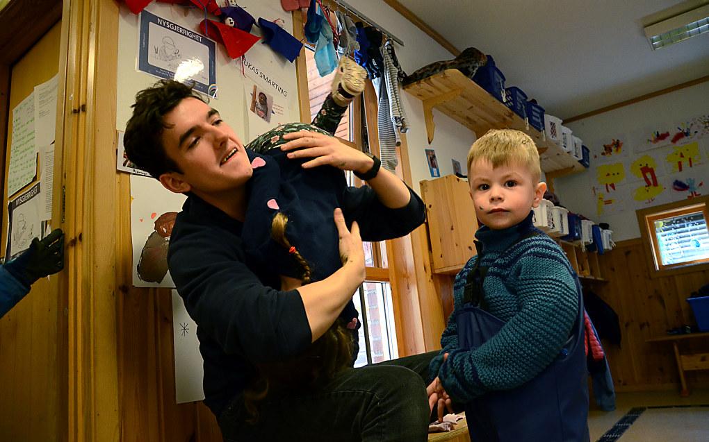 – Å være mann i barnehage gjør deg automatisk til et klatrestativ, sier Vetle Velstad med Lea hengende over skulderen. Nathaniel venter på å få hjelp med påkledningen. Foto: Kari Oliv Vedvik