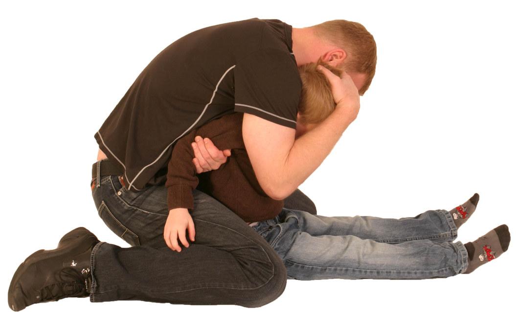 Her er noen råd til hvordan man kan håndtere en truende situasjon. I grepet som er vist her holdes begge armene til barnet med den ene armen din. Hodet stabiliseres for å avverge skalling og skjerme barnet. Foto: Verge Opplæring