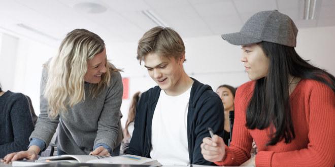 To elever i videregående opplæring sammen med en lærer.