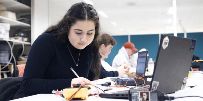 En elev på videregående sitter og jobber ved pc-en. Hun sitter alene. I bakgrunnen ser vi flere elever som også jobber.