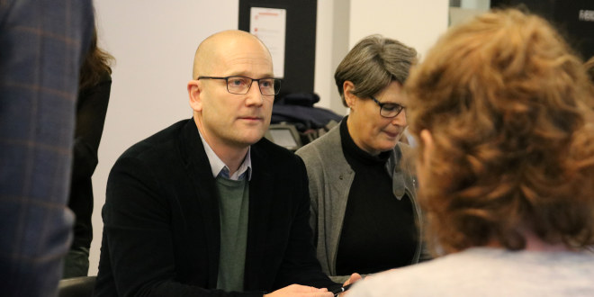 Mann uten hår med briller i hvit skjorte og dressjakke sitter ved et bord.