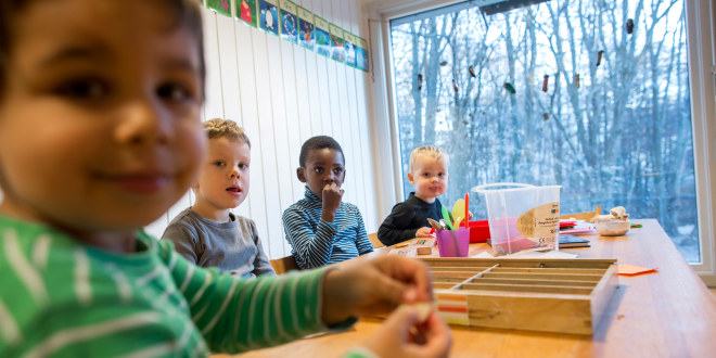 Fire barn i barnehagen rundt et stort bord.
