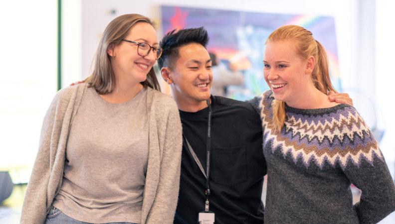 Bilde av tre medlemmer av Pedagogstudentene som ler mens de holder rundt hverandre under Oppstartshelgen 2018.