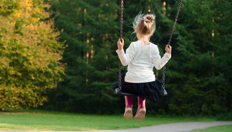 Illustrasjonsfoto: Liten jente sitter på huske i fart med ryggen til. Foto: Skitterphoto/ hentet fra Pexels.com.