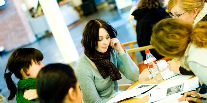 Studenter sitter rundt et bord med ark og jobber.