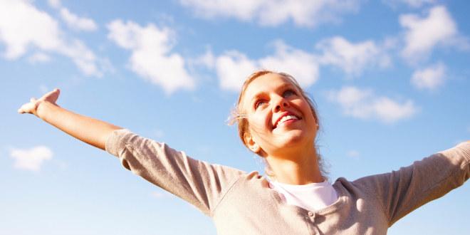Ung kvinne med hendene i været på solfylt dag.