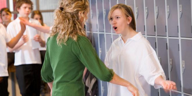 Lærer og tenåringselev er uenige og diskuterer.