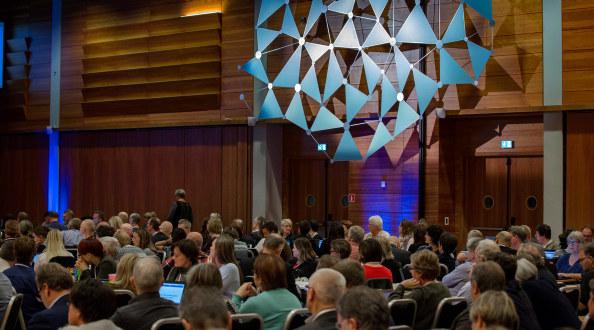 landsmøtesalen med delegater som sitter og lytter. Utsmykking på veggen bak.