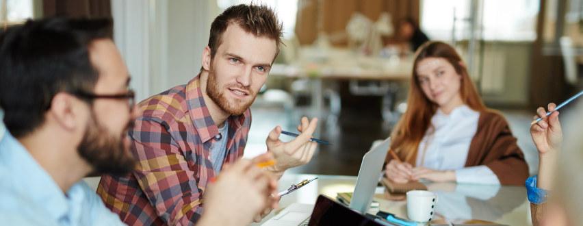 Flere personer i møte rundt et bord. Pen mann i fokus.