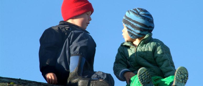 To gutter i barnehagealder sitter på en stein og prater sammen