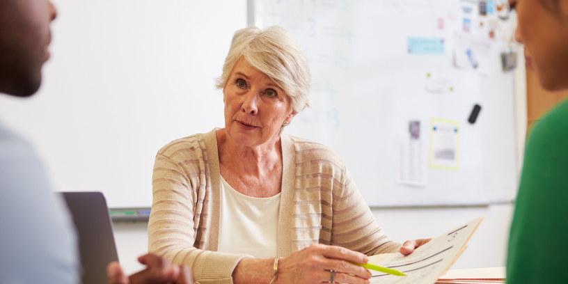 Lærer i samtale med to andre, enten voksne elever eller kolleger