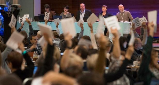 Landsmøtesal med delegater som har hender i været. De stemmer. På scenen bak sitter ordstryrerbordet og ser utover forsamlingen.