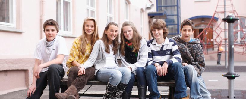 En gruppe smilende elever sammen i skolegården