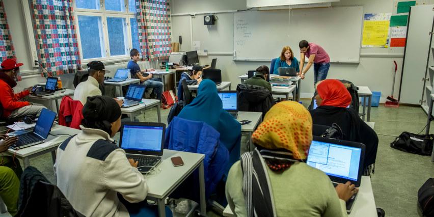 Voksne elever i et klasserom. Sitter ved pultene.