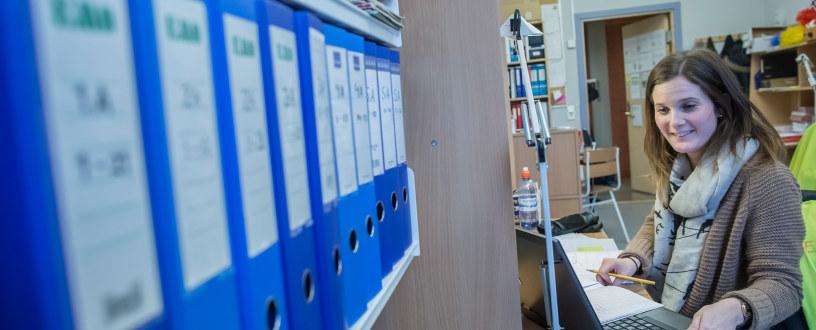 Lærer sitter ved kontorarbeidsplass og jobber på pc. I forgrunnen er det en rekke ringpermer