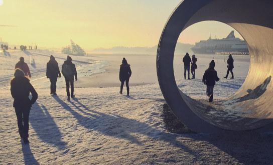 Vinterdag ved havna i Oslo, mennesker i motlys og snø og lange skygger