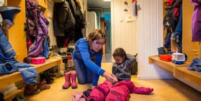 Dame i barnehage hjelper liten gutt med vinterdressen. Begge sitter på gulvet i garderoben.
