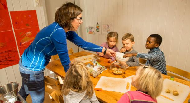 Barn sitter rundt et bord en barnehagelærer deler poteter med dem