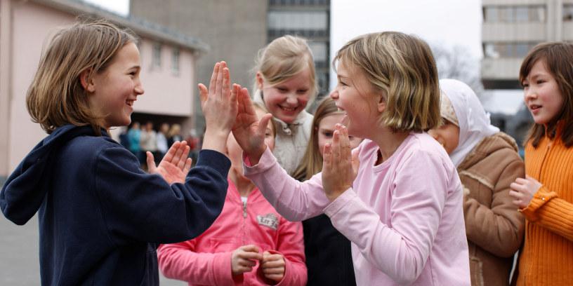 En gruppe jenter i skolegården leker i et friminutt