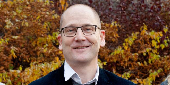 Portrett av en smilende Steffen Handal med en bakgrunn av høstfarget løv