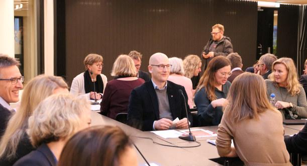 Folk sitter rundt et forhandlingsbord. En smilende Steffen Handal sitter i midten.