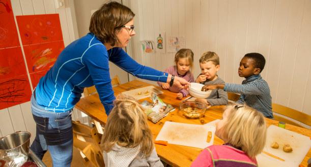 Bilde fra en barnehage der fem barn sitter rundt et bord og skjærer poteter. En kvinnelig barnehagelærer deler ut poteter.