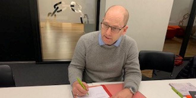 Steffen Handal skriver under avtalen.