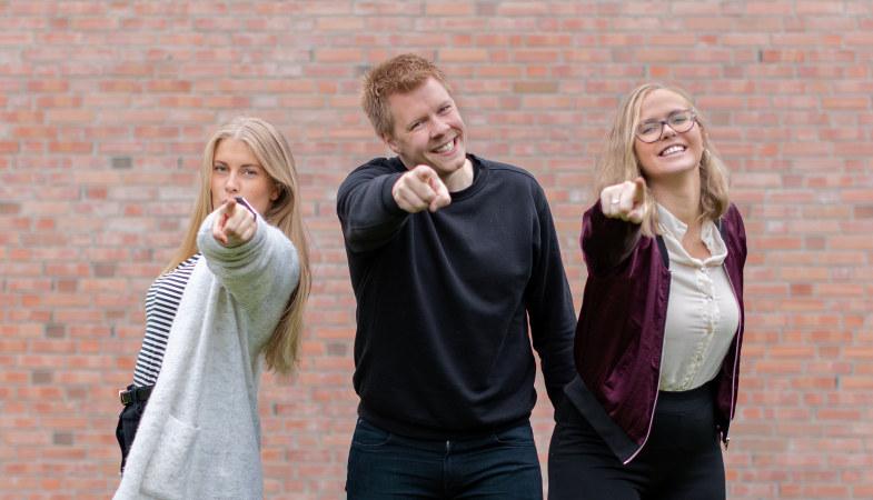Bilde av tre personer på rad, to damer og en mann i midten, som alle peker mot deg. På bilde: valgkomiteen i Pedagogstudentene for perioden 2019/2020. F.v.: Aud-Marit Sellereite, Ruben Amble Hirsti og Øyvor Fossli.