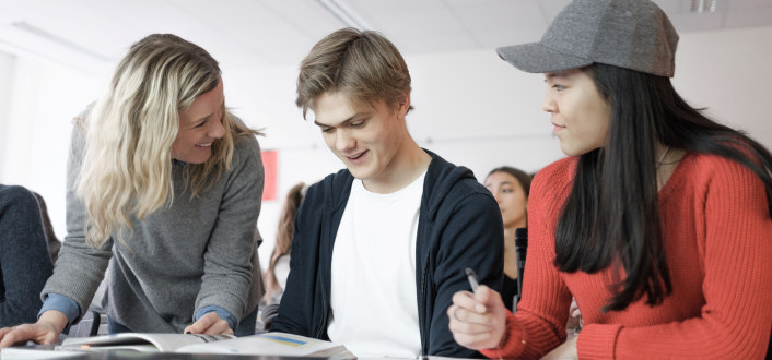 En kvinnelig lærer står og snakker med to elever ved deres pult. De smiler og gutten ser ned i en bok.
