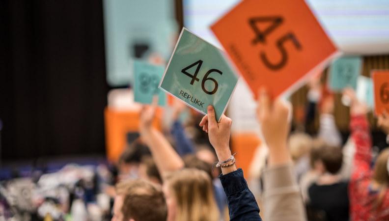 Bilde fra votering, mange hender som holder delegatskilt opp.  Foto: Chris-Håvard Berge/Oclin for Pedagogstudentene